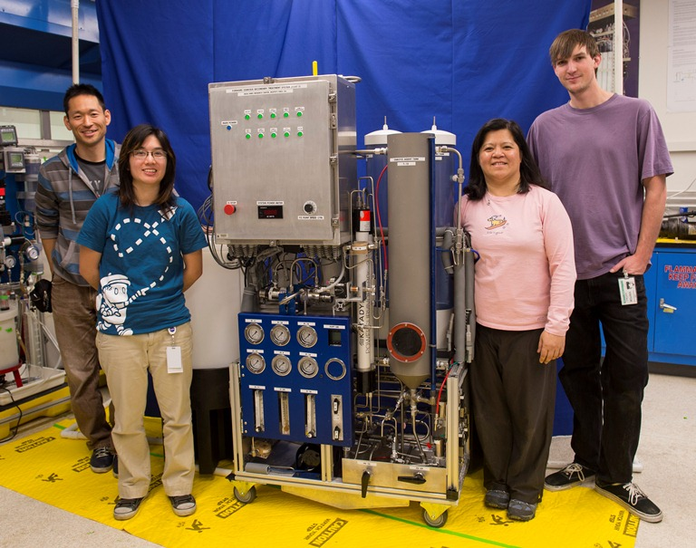 Water recycling system with team members standing beside system.