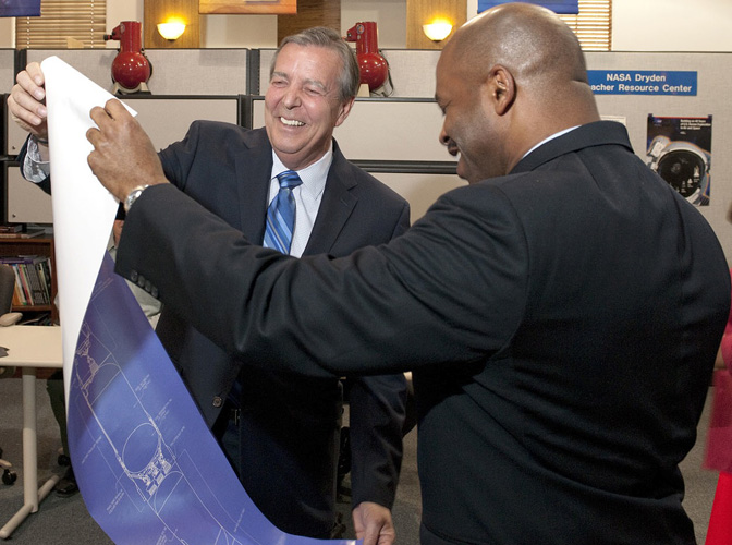 Mayor James Ledford of the City of Palmdale and NASA's education chief Leland Melvin got a laugh out of a poster depicting the