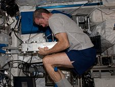 Canadian Space Agency astronaut Chris Hadfield works with the Space Linear Acceleration Mass Measurement Device (SLAMMD) in the Columbus laboratory of the International Space Station. (NASA)