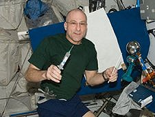International Space Station Expedition 30/31 flight engineer Don Pettit poses with a drinking water container, two syringes and a knitting needle at a workstation in the Harmony node. A video camera is set up to record his activities. A homemade Van de Graaff generator also is in view. (NASA)