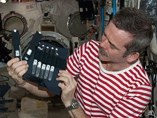 Canadian Space Agency astronaut Chris Hadfield holds bubble detectors for the RaDI-N 2 investigation in the International Space Station's Kibo laboratory. This investigation measures neutron radiation levels onboard the space station. It uses bubble detectors as neutron monitors, which have been designed to only detect neutrons and ignore all other radiation. (NASA)