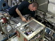 NASA astronaut Kevin Ford, Expedition 34 commander, performs maintenance on the Amine Swingbed in the Destiny laboratory. (NASA TV)
