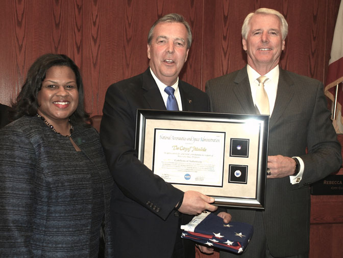 An American flag and pins representing NASA and Palmdale that were flown on space shuttle Endeavour's final ferry flight are presented to the city of Palmdale.