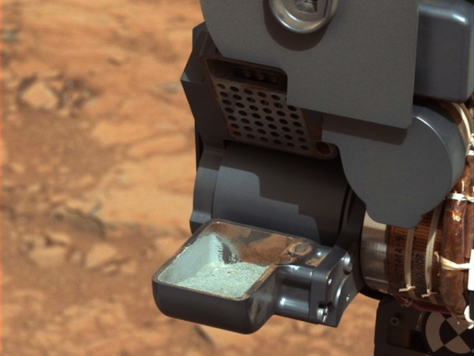 This image from NASA's Curiosity rover shows the first sample of powdered rock extracted by the rover's drill. The image was taken after the sample was transferred from the drill to the rover's scoop. In planned subsequent steps, the sample will be was sieved, and portions of it delivered to the Che