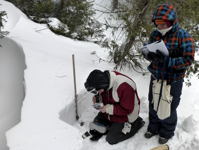 Two History of Winter (HoW) participants use a magnifying lens to observe grains of snow from a pit they dug in Cascade Lake, Lake Placid, New York, on Feb. 12, 2013.