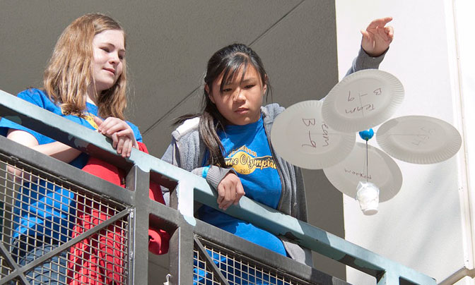 Two students from Jacobsen Middle School in Tehachapi carefully release their entry in the Science Olympiad's Rotor Egg Drop competition from the second story of a college building.
