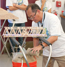 A Science Olympiad volunteer carefully adds more sand to a bucket carrying more than 25 lbs. of sand suspended from a popsicle-and-glue truss during the Boomilever bridge building competition.