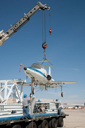 Workmen carefully guide the first of the T-38s into place as it is hoisted onto its pallet.