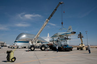 As the Super Guppy awaits its cargo in the background, workmen secure the second T-38 to its transport pallet.