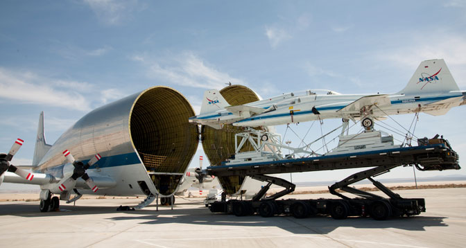 Two retired NASA T-38 trainers mounted on a transport pallet atop a mobile transporter are positioned for loading aboard NASA's Super Guppy prior to ferrying them to El Paso, Texas, for disassembly.