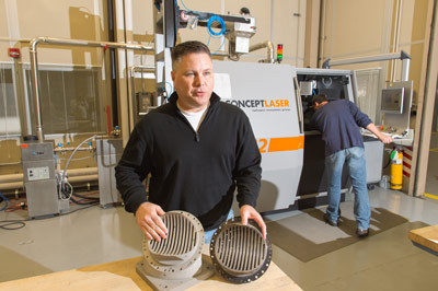 Andy Hardin, SLS subsystem manager for liquid engines, compares the process of creating a rocket engine part using traditional manufacturing and welding, at right, and making one using Selective Laser Melting, or SLM, at left.