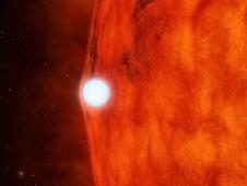 Artist's concept depicts a dense, dead star called a white dwarf crossing in front of a small, red star