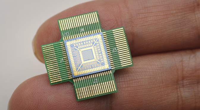 A silicon-based sensing chip, which consists of 64 nanosensors, on a person's fingertips.
