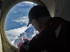 Mark Buesing, science teacher at Libertyville High School in Libertyville, Ill., takes a photograph out the window of NASA's P-3B during a mission to study glaciers in southeast Greenland on Apr. 8, 2013.