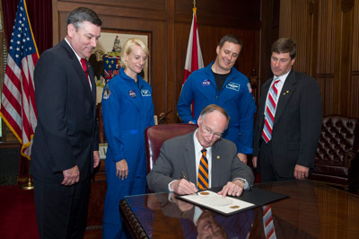 Alabama Gov. Robert Bentley signs a proclamation declaring April 18, 2013, 'NASA Day in Alabama.' Looking on, from left, are Marshall Space Flight Center Director Patrick Scheuermann, astronauts Kathleen 'Kate' Rubins and Jack Fischer, and State Sen. Bill Holtzclaw of Madison.