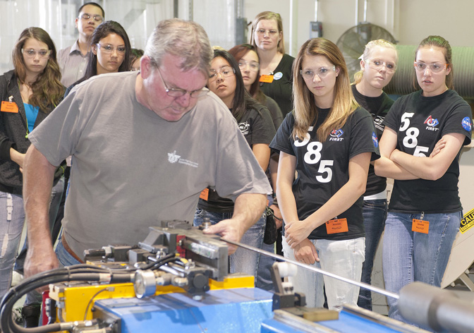 Members of the Tehachapi High School Cyber Penguins robotics team 585 watch intently as technician Jerry Cousins demonstrates the CNC tube bending machine in Dryden's experimental fabrication machine shop.