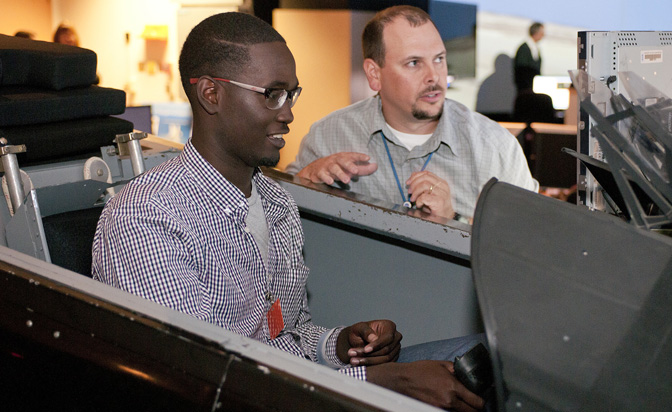 Eastside High School student Wilfredo Whitaker checks out his abilities in flying an F/A-18 in the flight simulator cockpit with Dryden simulation engineer Brian Spivey.
