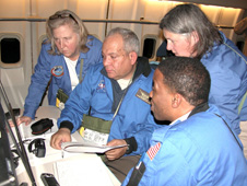 Airborne Astronomy Ambassadors (from left) Constance Gartner, Vince Washington, Ira Hardin and Chelen Johnson review data at the educators' workstation aboard the SOFIA observatory during an astronomy flight on the night of Feb. 12-13, 2013.