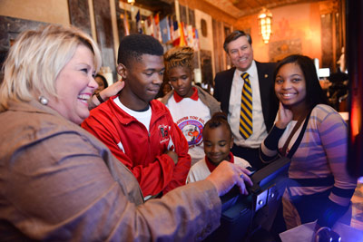 Students visiting the Louisiana Capitol for 'NASA Day in Baton Rouge' line up to pose for a virtual photo of themselves in a space suit on a NASA mission. Marshall Director Patrick Scheuermann, second from right, looks on as the students are assisted by Shannon Raleigh.