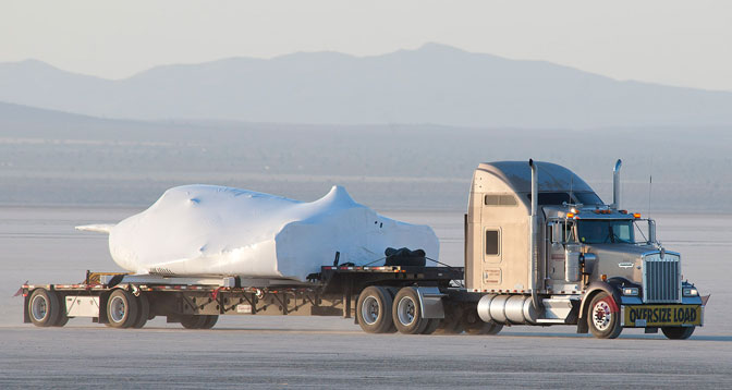 With its wings and tail structure removed and shrouded in protective plastic wrap, Sierra Nevada Corporation's Dream Chaser engineering test vehicle is hauled across the bed of Rogers Dry Lake at Edwards Air Force Base, Calif., to NASA's Dryden Flight Research Center May 15, 2013.
