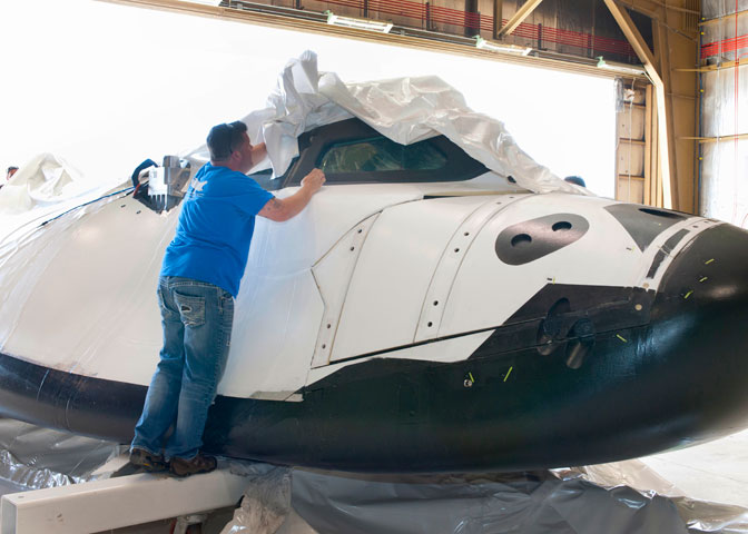 Plastic wrapping that protected Sierra Nevada Corporation's Dream Chaser flight test vehicle during its overland transport from Colorado is carefully removed by Dream Chaser crew chief Christian White.