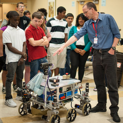 Independent robot builder Mark Curry, right, answers questions from 8th-graders from Sullivan Middle School in Lowell, Mass., about his robot during the NASA-WPI Sample Return Robot Centennial Challenge, held June 15, 2012, at the Worcester Polytechnic Institute.