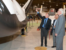 Former NASA space shuttle astronaut Steve Lindsey, now Director of Flight Operations for Sierra Nevada Corporation, points out features of the firm's prototype Dream Chaser flight test vehicle to NASA Administrator Charlie Bolden and Patrick Stoliker.