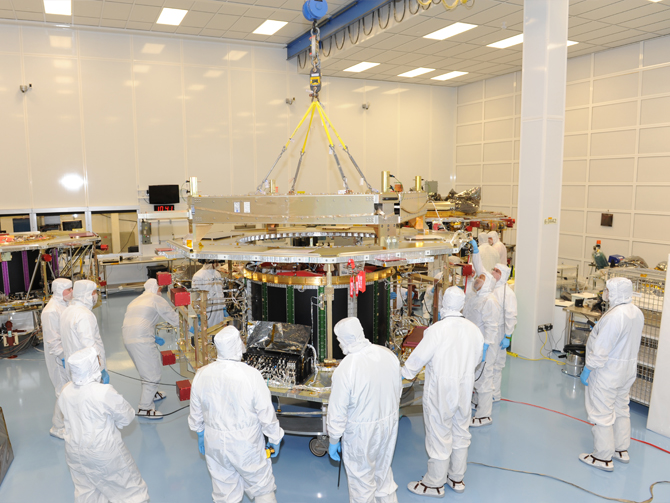 Magnetospheric Multiscale mission engineers, seen here in white cleanroom suits, integrate the fourth and final instrument deck onto the thrust tube, which houses the propulsion module, officially making it an observatory.