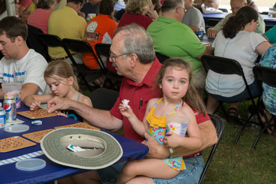 Ron Cantrell, quality assurance team lead in Marshall's Safety & Mission Assurance Directorate, assists his granddaughters Lauren Pierce, on his lap, and Carolyn Porter, left, with their bingo cards during the picnic.