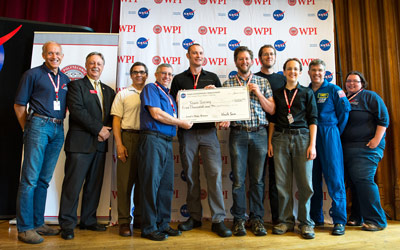 A NASA Centennial Challenges first-prize, level 1 check is presented to team Survey for successfully completing level 1 of the NASA 2013 Sample Return Robot Challenge.