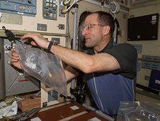 Expedition Six Flight Engineer Don Pettit uses a chemical/microbial analysis bag to collect water samples from the Potable Water Heater in the Zvezda Service Module on the International Space Station. (NASA)