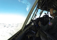 NASA pilot Jeff Chandler looks out at the sea ice during a flight in NASA's C-130