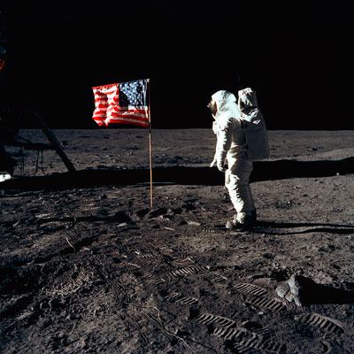 "Lunar module pilot Edwin ""Buzz"" Aldrin Jr. regards the deployed United States flag during an Apollo 11 extravehicular activity (EVA) on the lunar surface."