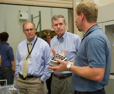 During a center tour on July 10, Steve Cash, NASA Marshall Space Flight Center's director of safety and mission assurance, and Bryan O'Connor, former astronaut and retired NASA chief of safety and mission assurance, listen as Ken Cooper, manager of Marshall Center's 3D printing facility, discusses¬ the process of 3D printing.