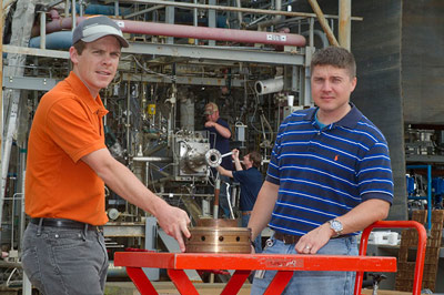 Test engineer Ryan Wall, left, and propulsion systems engineer Greg Barnett prepare a rocket injector made using the 3-D printing or additive manufacturing process for a hot-fire test at NASA's Marshall Space Flight Center.