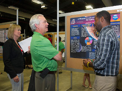 Dawid Yhisreal-Rivas, right, a senior from the University of Texas in El Paso, explains his research during his NASA summer internship to Marshall Center Deputy Director Teresa Vanhooser, left, and Chris Singer, director of Marshall's Engineering Directorate.