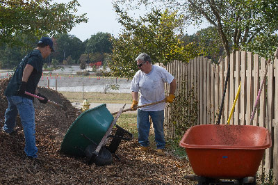 Tim Flores, left, stages integration manager with the Space Launch System (SLS) Program; and D.K. Hall, core stage lead also with SLS, help haul mulch at the CASA Community Garden in Huntsville as part of the Marshall Center's CFC Community Service Days.