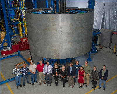 Members of the Dynetics and Flight Programs and Partnerships teams stand in front an Advanced Booster Demonstration Cryogenic Tank Test Article on the Vertical Weld Tool for trimming and friction stir welding.