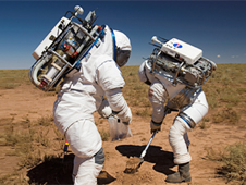 Two people dressed in spacesuits work in the desert