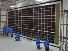 Engineers at Deployable Space Systems Inc. pose with their Mega-ROSA solar array, designed to roll out like a carpet. The design is one of two concepts now in consideration as part of NASA's Solar Electric Propulsion effort. (Image: DSS Inc.)