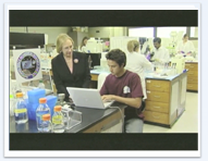 A teacher assists a student in a lab