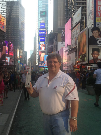 Bruce Askins, infrastructure management lead for the SLS Program at the Marshall Center, holds a paper model of the SLS in New York City's Times Square.