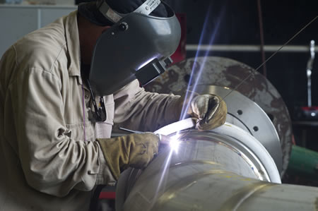 A welder at NASA's Stennis Space Center works on a portion of piping to be installed on the A-1 Test Stand for RS-25 rocket engine testing.