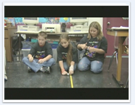 Three children work with spools that spin on the floor