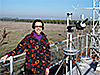 Anne Thompson poses on a rooftop with various remote sensing equipment