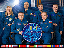 The Expedition 37 crew poses in front of a picture of the space station in orbit