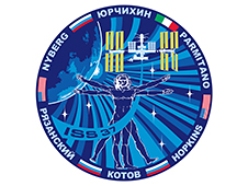 A round mission patch with the crew members' names and flags from their home countries circling the edge. The center of the patch features the space station in orbit and Leonardo da Vinci's Vitruvian Man drawing.