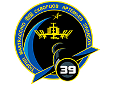 A round mission patch with the crew members' names around the edge. The center of the patch features the space station and a Soyuz spacecraft with number 39
