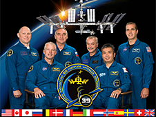 The Expedition 39 crew poses in front of a picture of the space station orbiting Earth