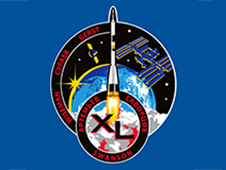 Round mission patch with smaller round patch overlaying its lower border. Patch has images of Soyuz, space station, cargo vehicle, sun on Earth's horizon, and Roman numerals XL